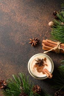 Feiertagsweihnachts-eierlikörgetränk im einmachglas mit zimt und muskatnuss auf braunem hintergrund