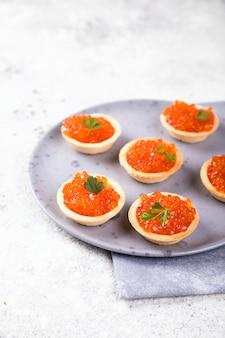 Feiertagszusammensetzung. roter lachskaviar im törtchen