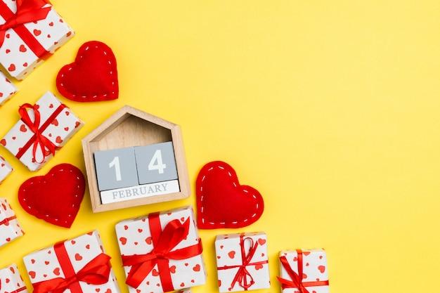 Feiertagszusammensetzung von geschenkboxen, von hölzernem kalender und von roten textilherzen auf tabelle mit leerem raum für ihr design. der vierzehnte februar. draufsicht von