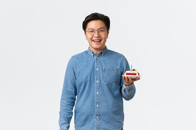 Feierurlaub und lifestyle-konzept lächelnder gutaussehender asiatischer mann mit hosenträgern, die optimistisch aussehen ...