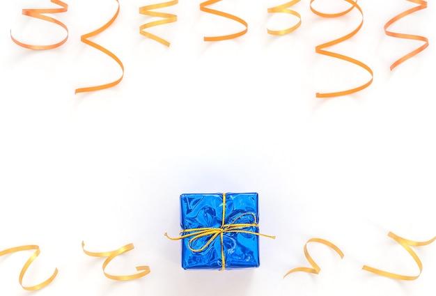 Feierweiß mit eingewickelter klassischer blauer geschenkbox mit goldband, helle party-luftschlangen.