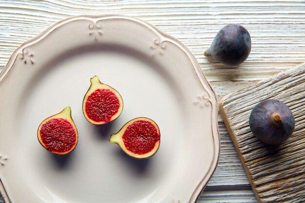 Feige rohe geschnittene feige trägt auf weißer platte auf weiß früchte