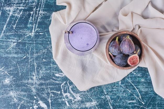 Feigen in einer schüssel mit einer tasse getränk auf blau.