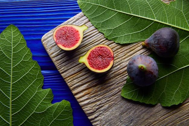 Feigen rohe geschnittene früchte und feigenbaumblätter auf blau