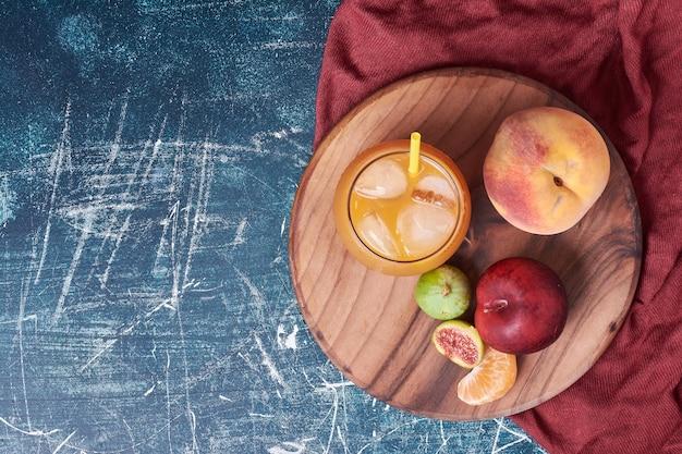 Feigen und pfirsich mit einer tasse getränk auf blau.