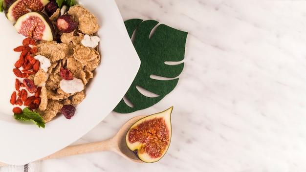 Feigenfruchtscheibe auf hölzernem schöpflöffel nahe geschmackvollem lebensmittel und gefälschtem monstera blatt über küchenarbeitsplatte