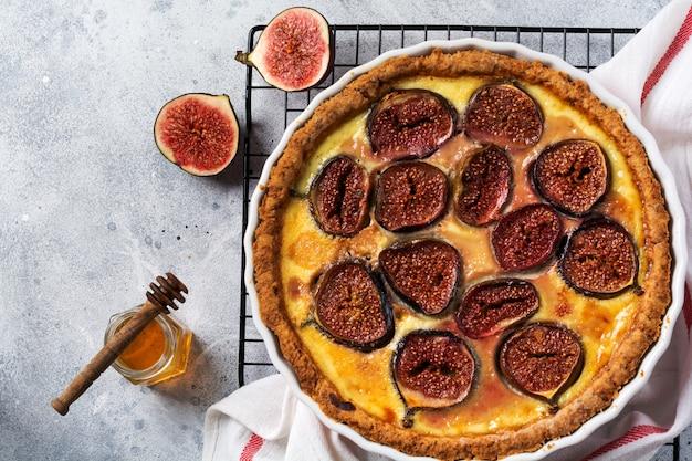 Feigenkuchen. köstliche torte mit frischen feigen und ziegenkäse auf rustikalem holztisch. ansicht von oben