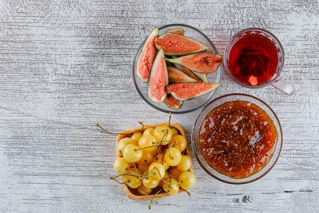 Feigenmarmelade mit feigen, kirschen, tasse tee in einer schüssel auf grungy, draufsicht.