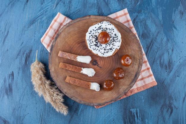 Feigenmarmelade und käsebrot an bord auf geschirrtuch, auf dem blauen tisch.