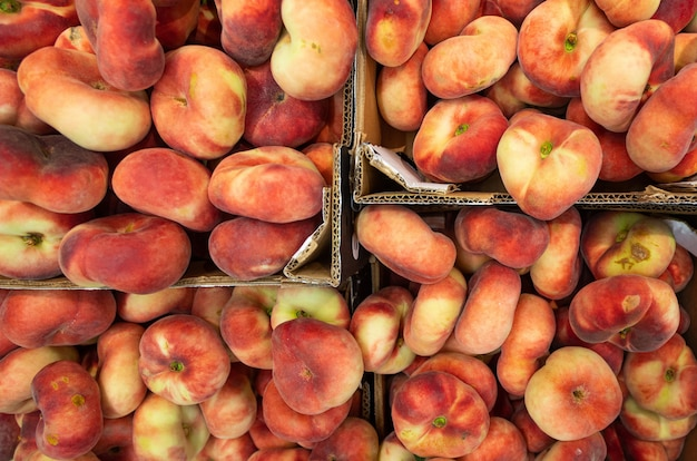 Feigenpfirsich, flache pfirsiche auf dem bauernmarkt oder im supermarkt. draufsicht, t-shirt für landwirtschaftsnachrichten oder illustration.