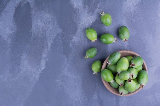 Feijoa früchte in einer holzschale auf blauer oberfläche