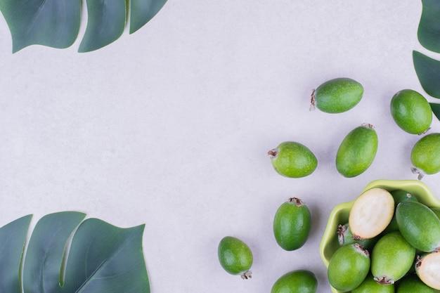 Feijoas in einer grünen tasse auf grauer oberfläche