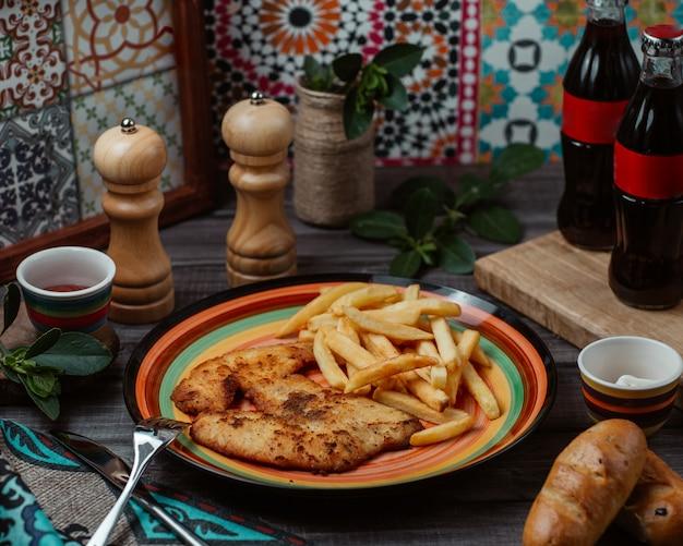 Fein gebratenes hähnchenfilet mit kräutern und pommes frites in einer bunten platte