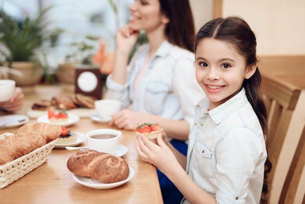 Feine glückliche familie, die kuchen in der cafeteria isst.