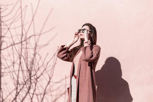 Feine junge frau richtet trendige sonnenbrille in der nähe der rosa wand auf atemberaubendes mädchenmodell mit langen haaren im eleganten frühlingsmantel mit stilvoller handtasche posiert an einem sonnigen tag in der nähe des vintage-gebäudes. liebenswerte frau.