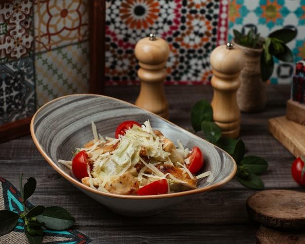 Feiner caesarsalat mit fein gehacktem parmesan und süßkirschen in einer rustikalen schüssel