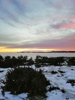 Feld bedeckt mit grün und schnee, umgeben vom wasser unter einem bewölkten himmel während des sonnenuntergangs