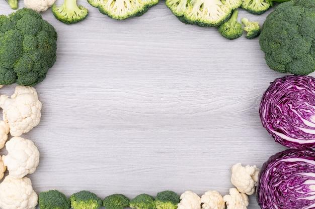 Feld des bunten gemüsebrokkoliblumenkohl-rotkohls mit kopienraum auf weißer holzoberfläche