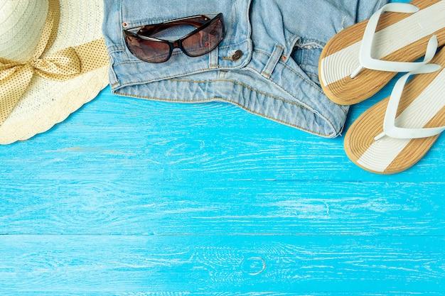 Feld elegante weibliche strohhuthefterzufuhr-jeanssonnenbrille auf blauem hölzernem hintergrund, copyspace für text, sommerferien.