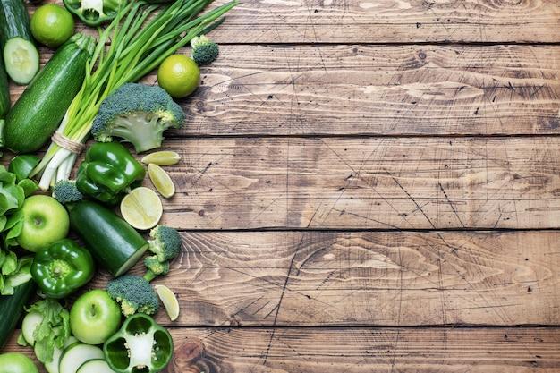 Feld frisches grünes gemüse und kräuter auf einem hölzernen hintergrund. kopieren sie platz.
