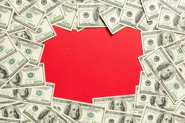 Feld gebildet von den dollar mit exemplarplatz in der mitte. draufsicht des geschäftskonzeptes auf rotem hintergrund mit kopienraum