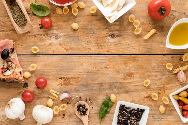 Feld gemacht mit italienischer pizza und bestandteilen über hölzernem schreibtisch