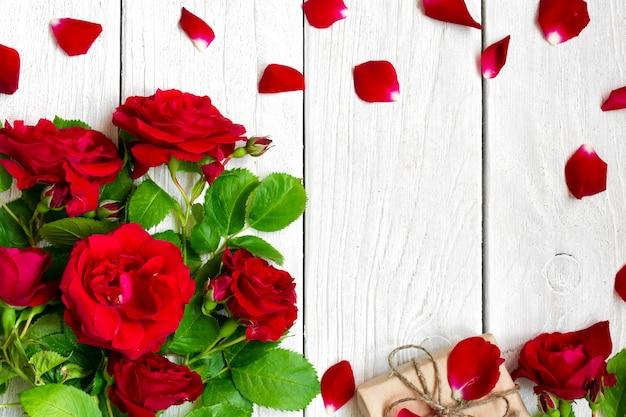 Feld gemacht vom blumenstrauß der roten rosen mit den blumenblättern und geschenkbox