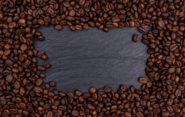 Feld gemacht von den röstkaffeebohnen auf schwarzer tabelle, draufsicht