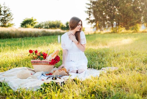 Feld in gänseblümchen, ein blumenstrauß. romantische picknickeinstellung im französischen stil. frau im baumwollkleid und im hut, erdbeeren, croissants, blumen auf decke, draufsicht. versammlungskonzept im freien.