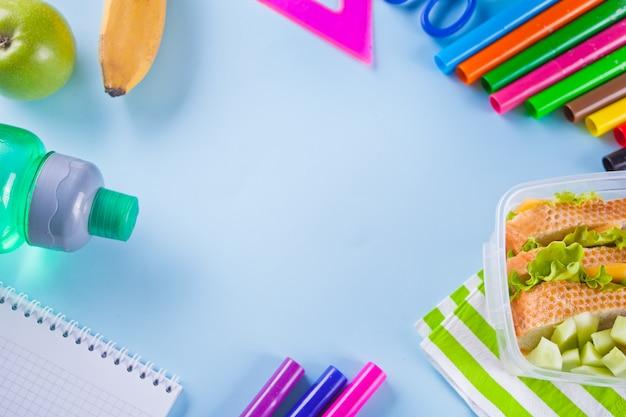 Feld mit bunten filzstiften, notizbuch, grüner apfel, sandwich auf blau