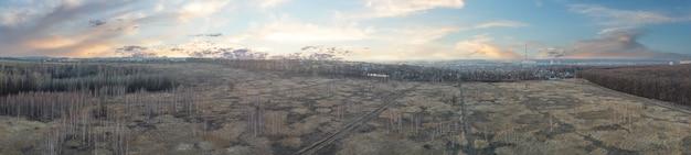 Feld mit trockenem gras im hintergrund der stadt und der rohre des kraftwerks. panorama