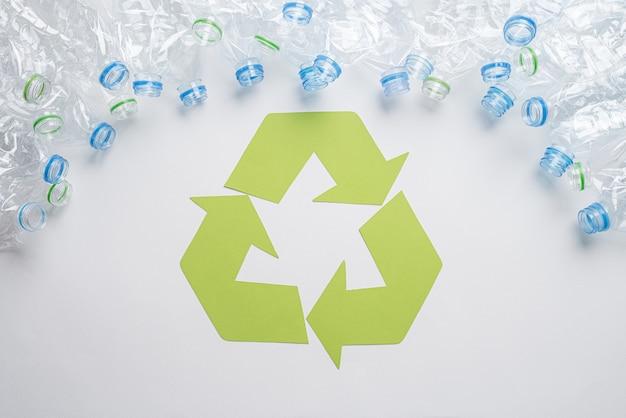 Feld von benutzten plastikflaschen mit der wiederverwertung des symbols