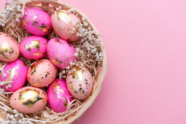 Feld von goldenen verzierten eiern ostern auf pastellrosahintergrund.