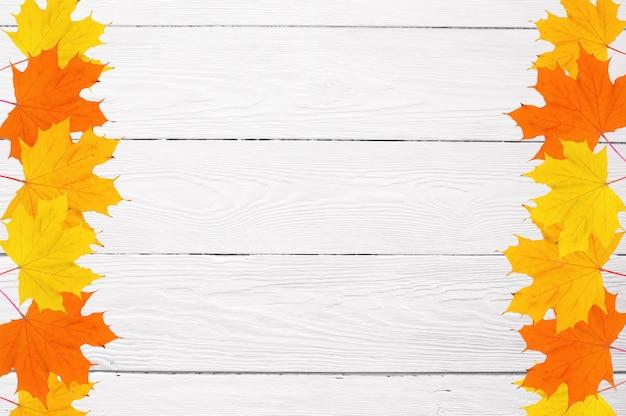 Feld von herbstahornblättern auf einem weißen hölzernen hintergrund- und kopienraum