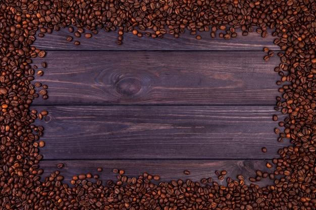 Feld von kaffeebohnen auf dunklem hölzernem hintergrund. draufsicht mit kopienraum