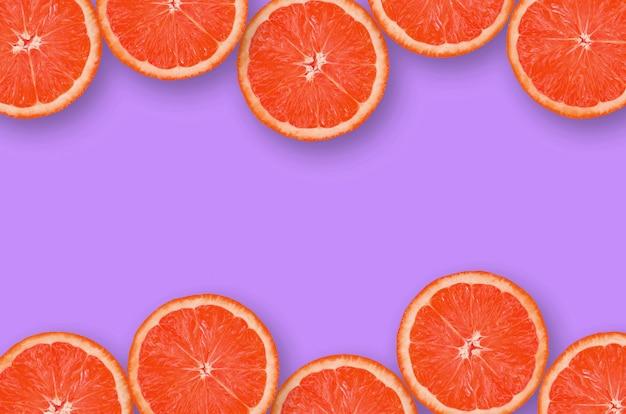 Feld von pampelmusenzitrusfruchtscheiben auf hellem purpur