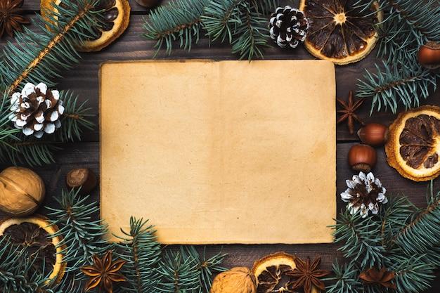 Feld von weihnachtsbaumkegel-orangen-nüssen auf dunklem hölzernem hintergrund. kopieren sie platz. flach liegen. altes papier für text.