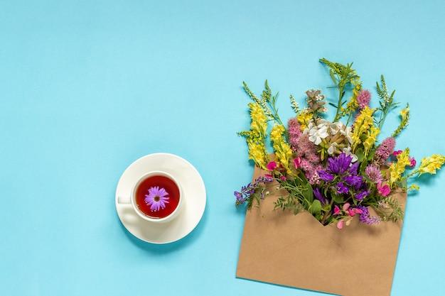 Feldblumen im handwerksumschlag und in der schale kräutertee