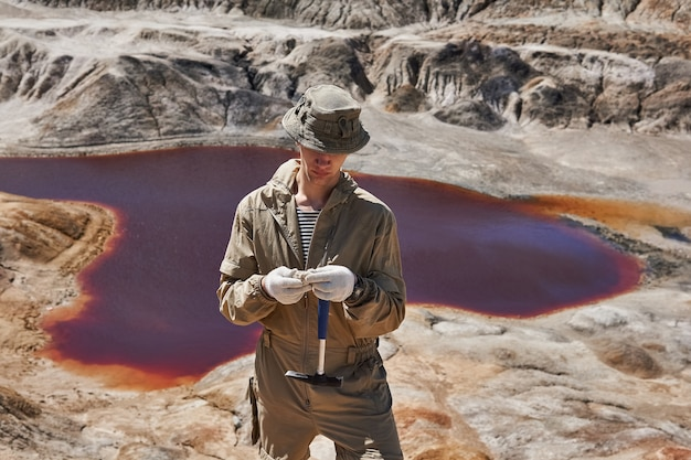 Feldexpeditionsgeologe untersucht eine mineralprobe gegen die schlucht mit einem salzsee