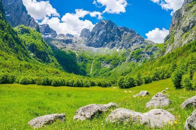 Feldweg durch eine malerische ebene zwischen den hohen bergen.