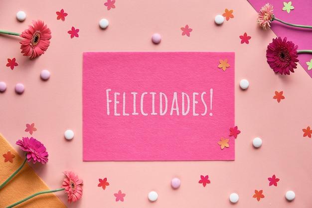 Felicidades bedeutet glückwünsche in spanischer sprache. lebendige flache lage mit gerbera-gänseblümchenblüten