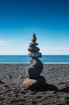 Fels des schicksals. ein stapel der steine auf dem schwarzen sandstrand in vik, island.