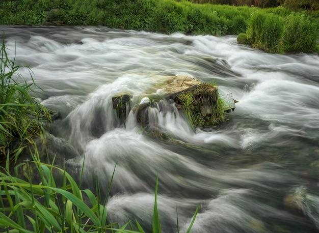 Felsbrocken im wasserriff des gebirgsflusses