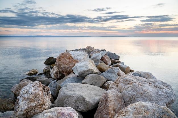 Felsen an der ägäischen seeküste bei sonnenuntergang, landen in der ferne in skala fourkas, griechenland