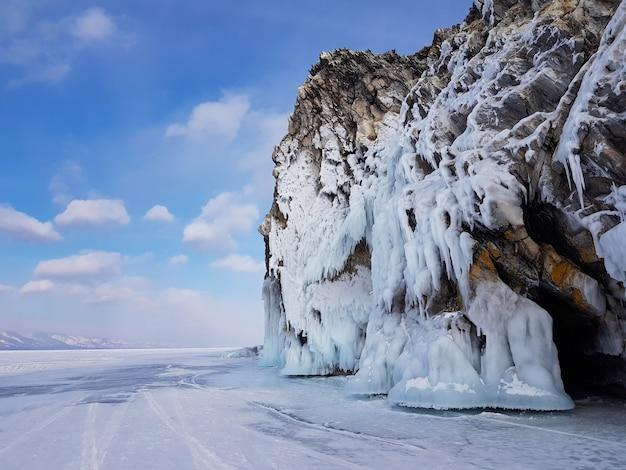 Felsen im eis auf dem hintergrund einer winterlandschaft an einem sonnigen tag mit einem schönen blauen himmel
