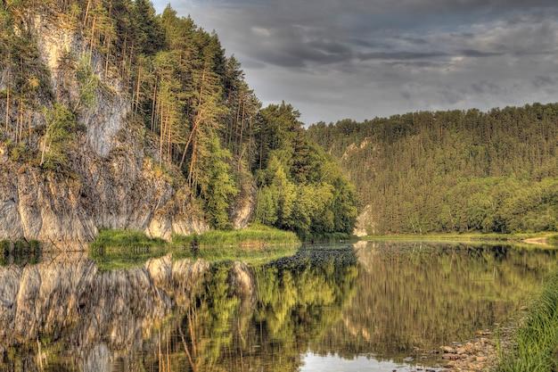 Felsen und wald spiegeln sich im fluss, bewölkter sommertag, südural, russland.