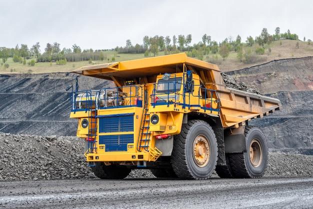 Felsentransport mit muldenkippern. großer gelber steinbruchwagen. transportindustrie.
