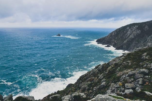 Felsige klippe von kap finisterre in galizien, spanien unter einem bewölkten himmel