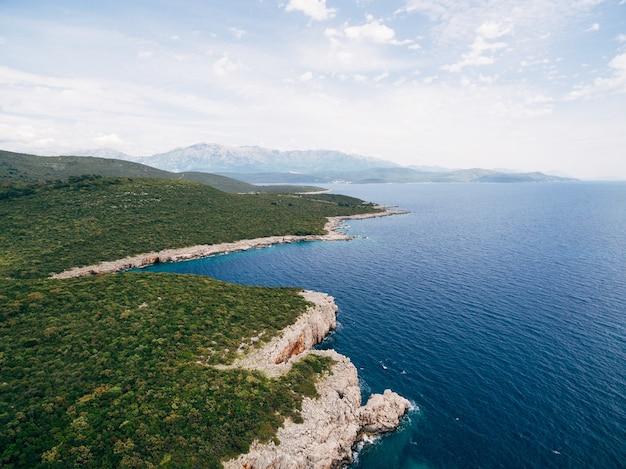 Felsige küste in der nähe von veslo camping in montenegro azurblaues wasser weiße wellen schlagen die felsen sonnig