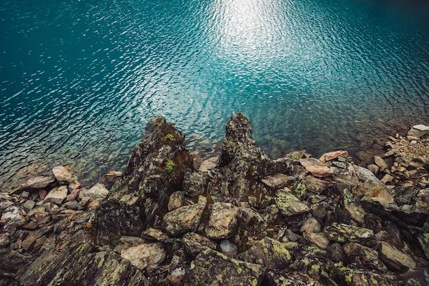 Felsige kueste. wasserrand. glänzende oberfläche des azurblauen bergsees. steiniger boden in transparentem wasser.